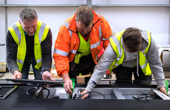 Photo of engineers at SIS Digital's Vision Park factory in Cambridgeshire completing the final assemply of a section of digital sign
